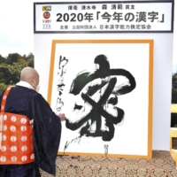 The head priest of Kiyomizu Temple in Kyoto puts the final touches on his rendering of mitsu, which was chosen as the kanji that best represented the mood of 2020. | POOL / VIA KYODO