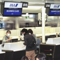 Passengers go through boarding procedures at an All Nippon Airways check-in counter for the airline's inaugural flight to Shenzhen at Narita Airport in Chiba Prefecture on Monday. | KYODO