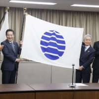Shinji Inoue (second from left), minister in charge of the 2025 World Exposition in Osaka, poses with the international expositions flag in Tokyo on Dec. 1 after the Paris-based Bureau of International Expositions formally approved plans for the 2025 World Exposition in its online general assembly the same day. | KYODO