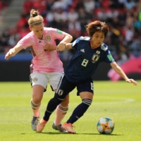 Nadeshiko Japan's Mana Iwabuchi (right) holds off Scotland's Kim Little during their Women's World Cup group stage match on June 14, 2019, in Rennes, France. | REUTERS