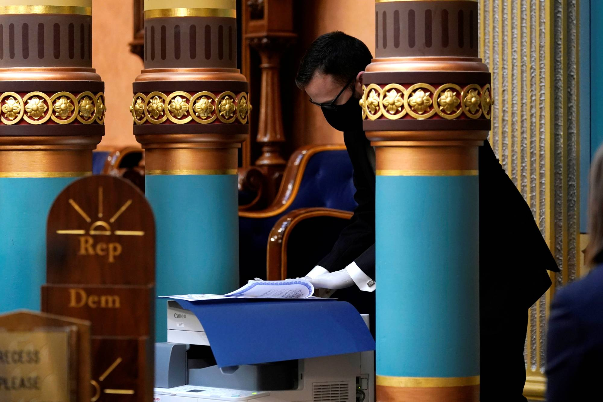 A staff member prepares the official Certificate of Votes for mailing after the Electoral College cast their votes at the state Capitol in Lansing, Michigan, on Monday. | POOL / VIA REUTERS