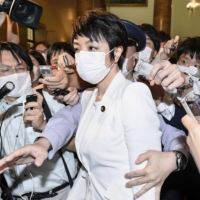 Upper House lawmaker Anri Kawai, the wife of former Japanese Justice Minister Katsuyuki Kawai, is surrounded by reporters after an Upper House plenary session in Tokyo on June 17. | KYODO