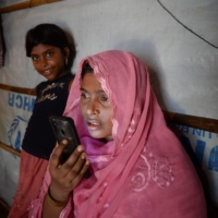 A Rohingya refugee Arofa Khatun, who tried to migrate with her two children to Malaysia to her husband, interacts with her spouse via video call at a makeshift shelter in Bangladesh. | AFP-JIJI