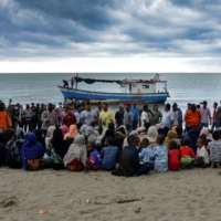 Rohingya migrants sit by the beach after their boat landed on the shores of Lancok village, Indonesia. Boatloads of Rohingya landing across Southeast Asia are victims of complex human trafficking networks run by a dizzying web of players, from crime bosses and corrupt cops to poor fishermen, rickshaw drivers and even Rohingya themselves. | AFP-JIJI