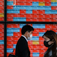 Pedestrians walk past an electronic board displaying the 225-issue Nikkei average on Wednesday.   AFP-JIJI