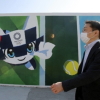 A man walks by a poster promoting the 2020 Summer Olympics in Tokyo last month. | AP