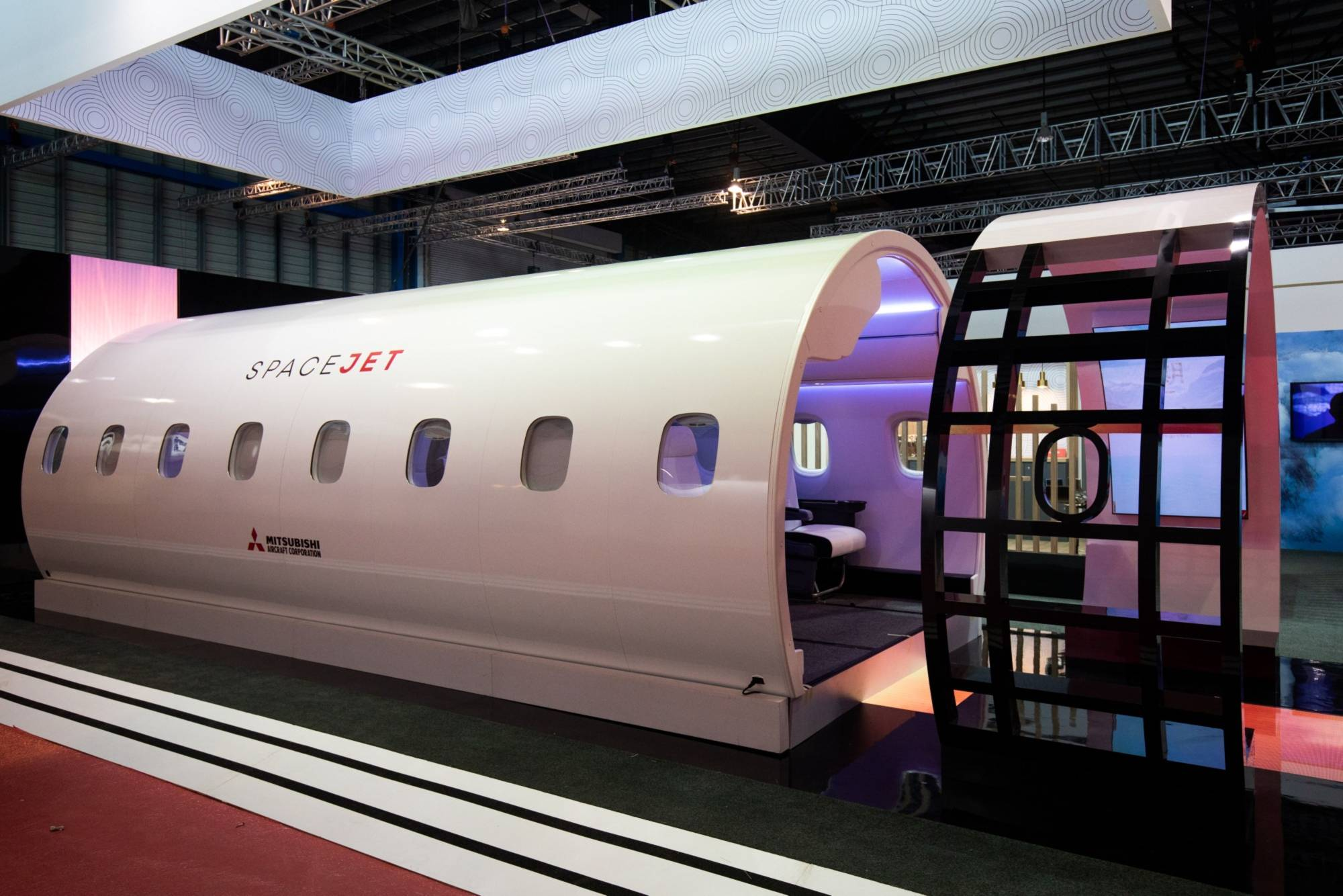 A model of SpaceJet regional jet, manufactured by Mitsubishi Heavy Industries Ltd., stands on display at the company's booth during a media preview day at the Singapore Airshow held at the Changi Exhibition Centre in Singapore February. | BLOOMBERG