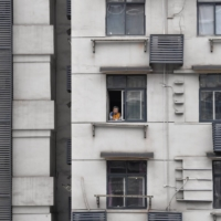 A man looks out of the window of a residential building in Wuhan, China, during lockdown on March 6. | REUTERS