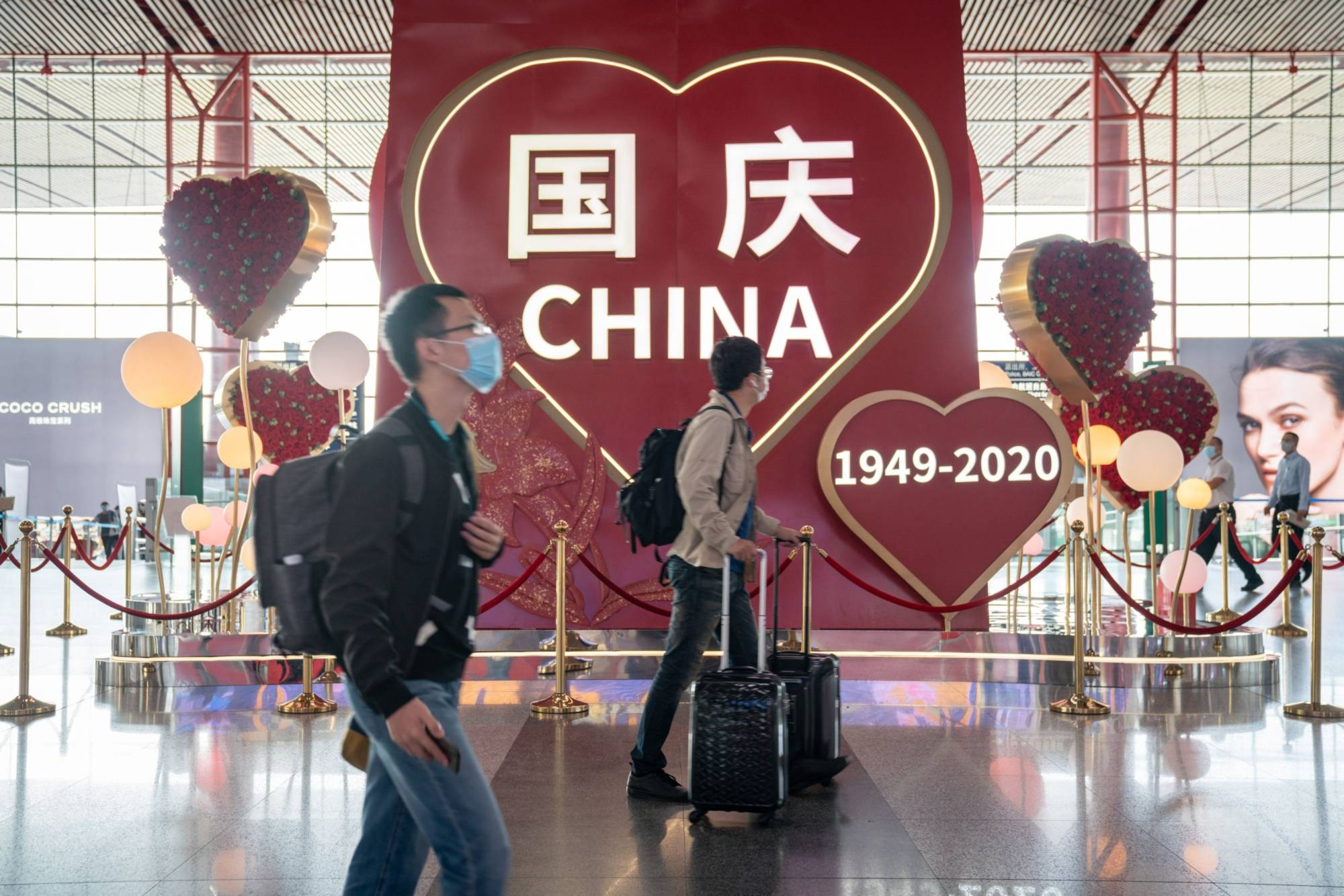 Travelers push their luggage past a sign celebrating National Day at Beijing Capital International Airport on Sept. 30. | BLOOMBERG