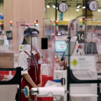 A retail assistant stands behind transparent plastic sheets at a checkout counter of supermarket group Aeon's shopping mall as the center reopens amid the COVID-19 outbreak in Chiba Prefecture in May. | REUTERS