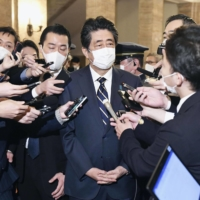 Former Prime Minister Shinzo Abe speaks to reporters at the Diet on Dec. 4 regarding allegations that his office illegally used political funds to pay for dinner parties. | KYODO