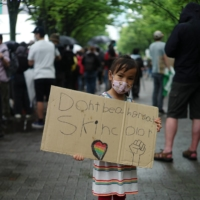 For the future: A young girl holds up a sign at Black Lives Matter solidarity march near Yoyogi Park in Tokyo on June 14.  | RYUSEI TAKAHASHI