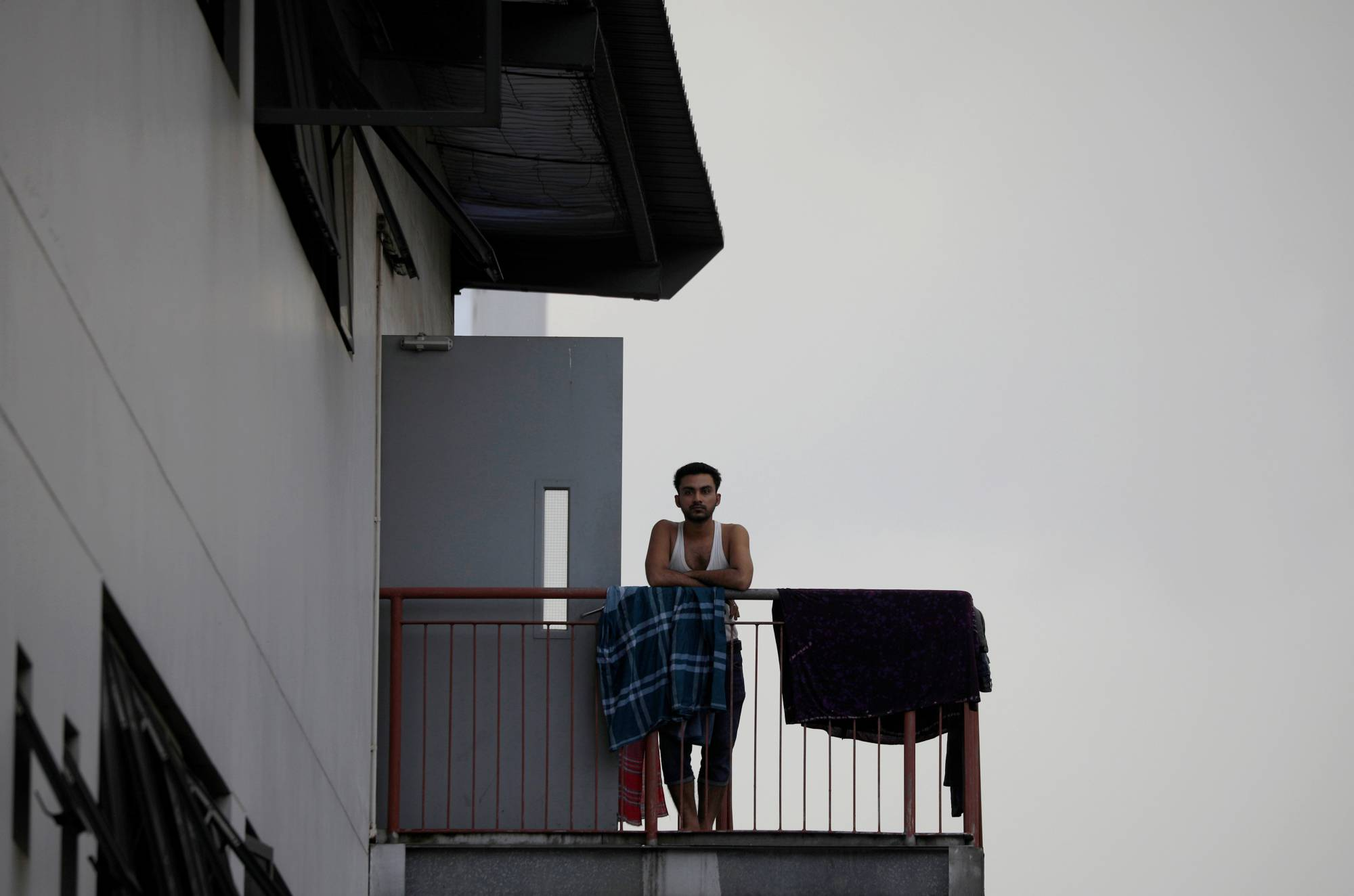 A migrant worker looks on from outside his room in a factory-converted dormitory in Singapore in May. | REUTERS
