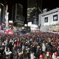 Crowds wait for the countdown near Shibuya Station on New Year's Eve last year. | KYODO