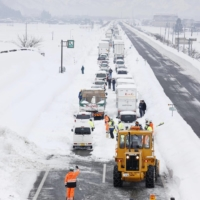 Vehicles are stranded on the Kanetsu Expressway in Minamiuonuma, Niigata Prefecture, on Friday after heavy snow hit a wide area along the Sea of Japan coast. | KYODO