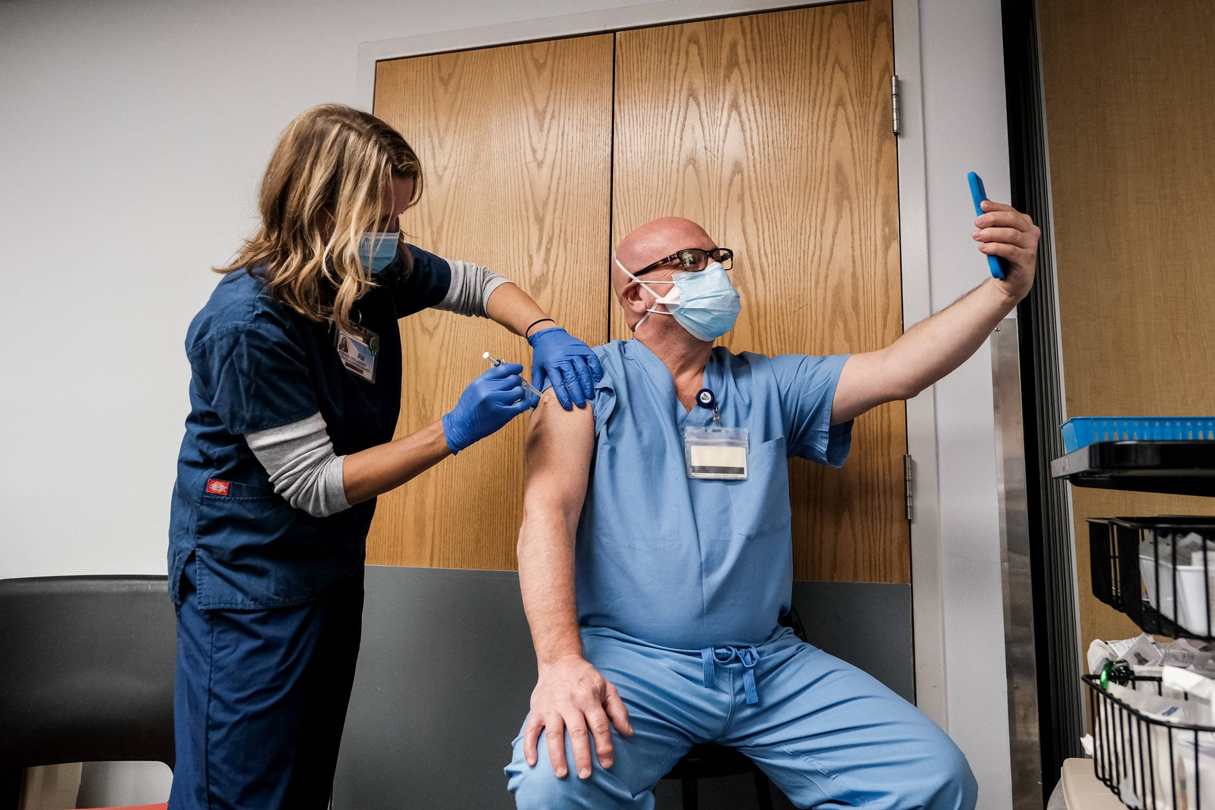 A health care worker makes a selfie while receiving a Pfizer-BioNTech COVID-19 vaccine at Virginia Hospital Center in Arlington on Wednesday. | MICHAEL A. MCCOY/THE NEW YORK TIMES