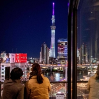 People look at Tokyo Skytree from an observation floor of a building in the Asakusa district of Tokyo on Thursday. | AFP-JIJI