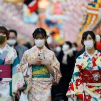 Women in kimono walk beneath decorations for the new year amid the coronavirus pandemic in Tokyo on Friday. | REUTERS