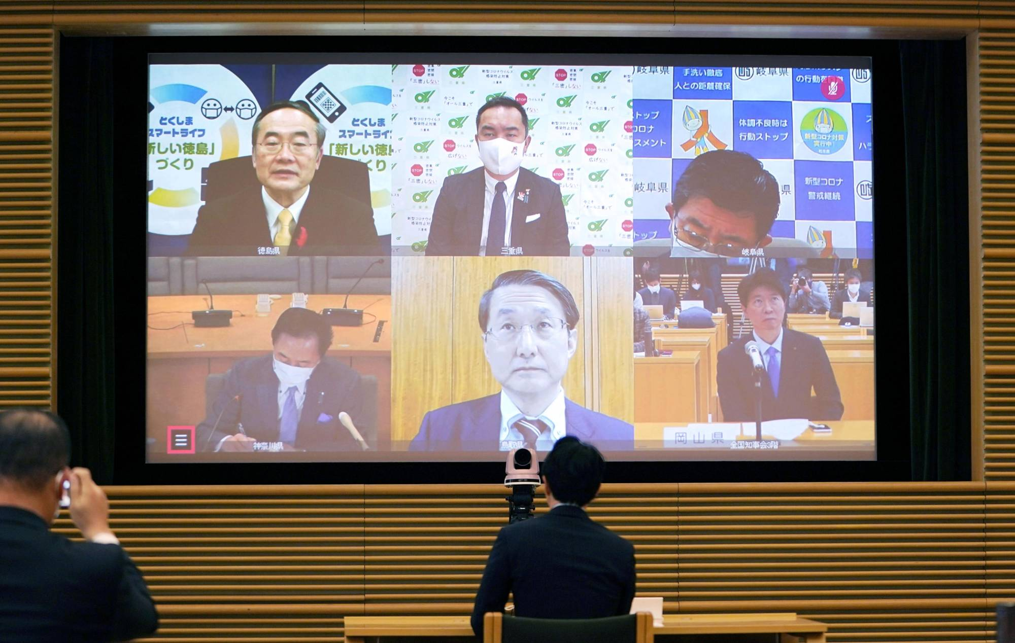 Tokushima Gov. Kamon Iizumi (above left), head of the National Governors' Association, addresses the association's online meeting held Sunday. | KYODO