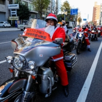 People dressed in Santa Claus costumes ride their motorbikes during the Xmas Toy Run parade to rev up the holiday spirit and rally against child abuse in Tokyo on Sunday. | REUTERS