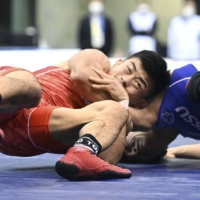 Kenichiro Fumita (left) attacks Ayata Suzuki in the 60-kg Greco-Roman final during the national wrestling championships at Komazawa Gymnasium on Sunday. | POOL / VIA KYODO