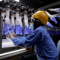 A worker inspects gloves at the Top Glove factory in Shah Alam, Malaysia, in August.  | REUTERS