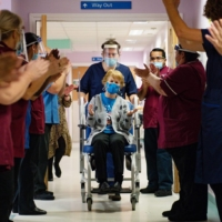 Margaret Keenan is applauded by staff after becoming the first person to receive the Pfizer-BioNtech COVID-19 vaccine at University Hospital in Coventry, central England, on Dec. 8, 2020. | POOL / VIA AFP-JIJI