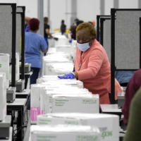 Boxes containing the Moderna COVID-19 vaccine are prepared for shipping at the McKesson distribution center in Olive Branch, Mississippi, on Sunday. | POOL / VIA AP
