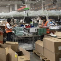 Employees pack orders at Alibaba's logistics arm Cainiao ahead of the Singles' Day shopping extravaganza this year. | BLOOMBERG
