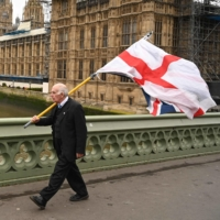 A man carries a flag of St. George, the English national flag, along with a Union Flag as he walks along Westminster Bridge by the Houses of Parliament in London in January. | AFP-JIJI