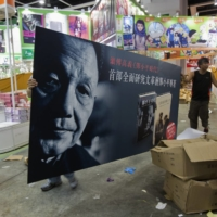 Workers carry an advertisement promoting the Chinese edition of 'Deng Xiaoping and the Transformation of China', written by Harvard University Professor Emeritus Ezra Vogel, during a media preview of the Hong Kong Book Fair in 2013. | REUTERS