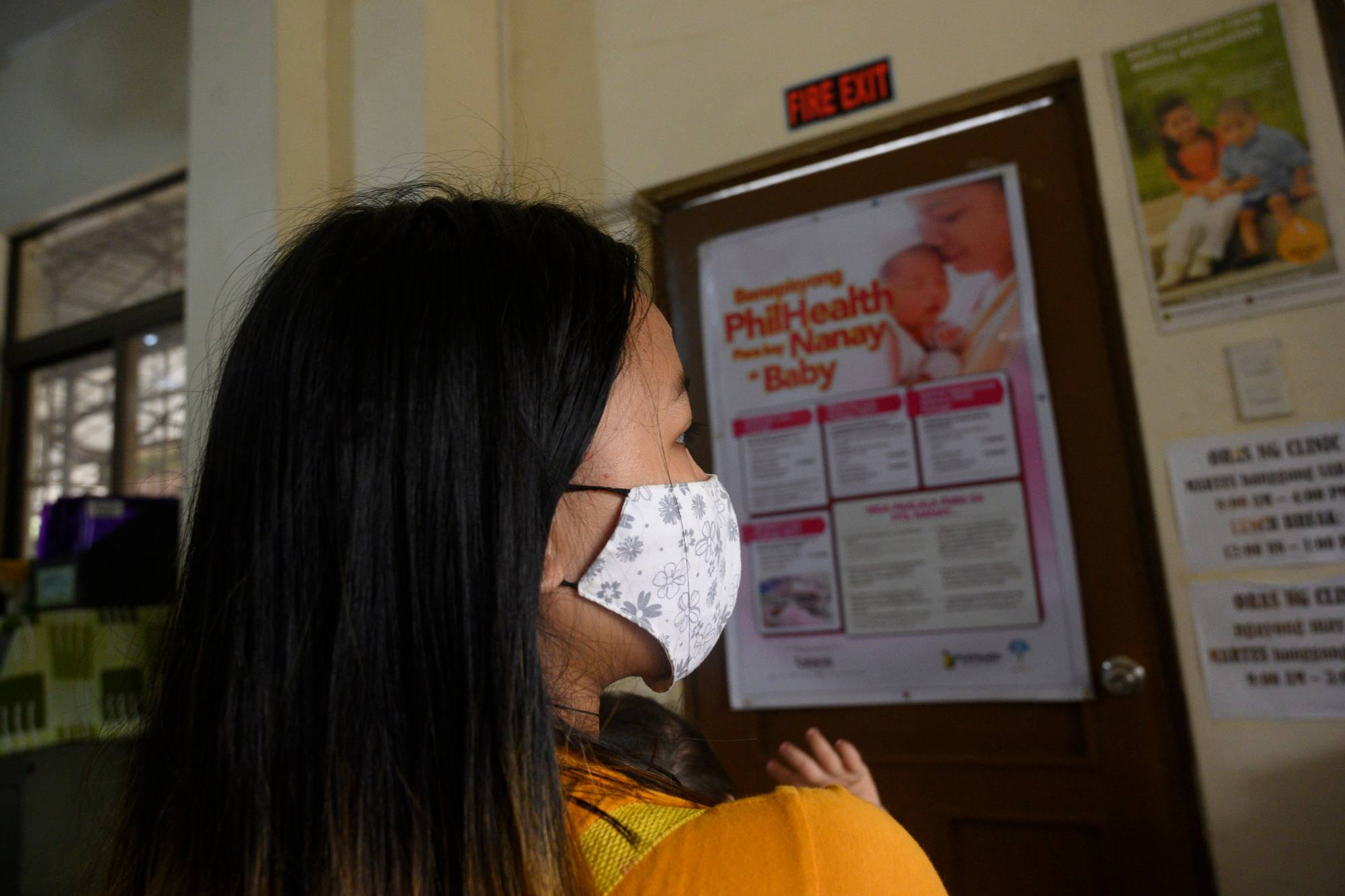 Donna Valdez, 15, whose name has been changed to protect her identity, carries her child at a health center in Manila on Dec. 2.   | AFP-JIJI