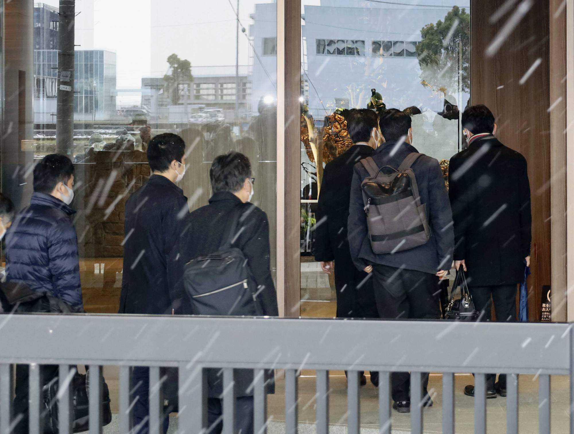 Officials enter the headquarters of Kobayashi Kako Co. in Awara, Fukui Prefecture, on Monday for on-site inspections. | KYODO