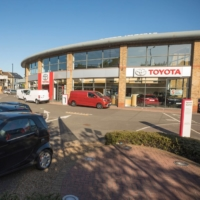 Parked cars block the entrance to a closed Toyota Motor Corp. dealership in London on April 20. Toyota will halt production in the U.K. and France from Tuesday due to transport delays caused by a mutant strain of coronavirus. | BLOOMBERG