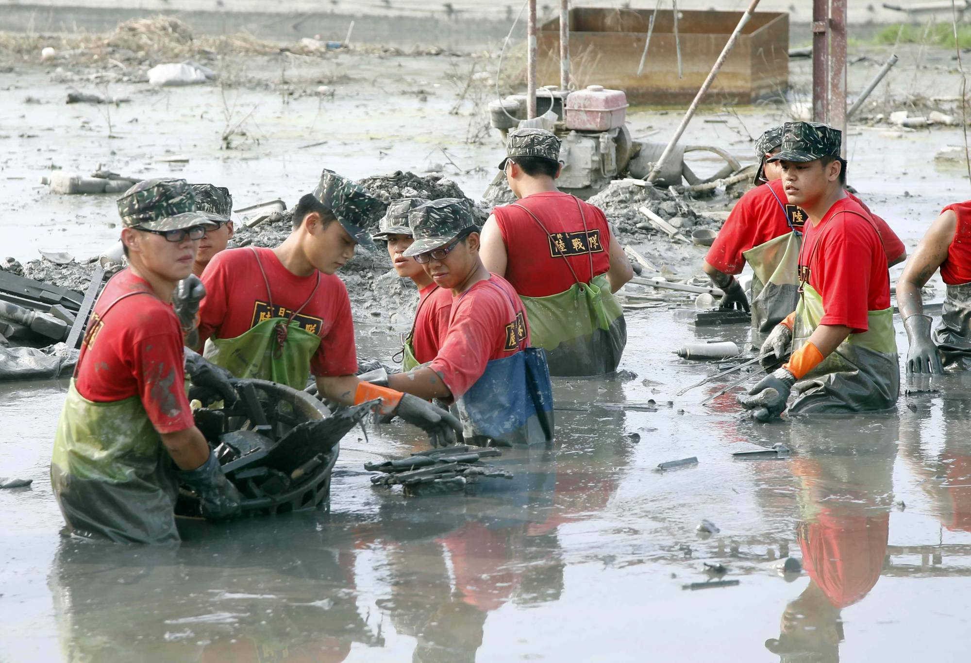Soldiers pick up rubbish and items on a flooded street following Typhoon Morakot in Pingtung County, southern Taiwan, on August 23, 2009. | TAIWAN MILITARY NEWS AGENCY / VIA REUTERS