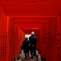 A couple walks through red-colored wooden torii gates at a shrine in Tokyo on Tuesday. | REUTERS