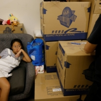 Eunis Lai, 12, rests as her father Willie packs up their belongings to be shipped to Scotland. | REUTERS