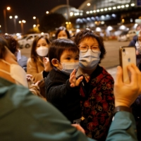 One-year-old Yanis Lai, who is emigrating to Scotland with her parents and siblings, and her grandmother, Ada, say goodbye to friends on a video call outside Hong Kong International Airport. | REUTERS