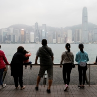 The Lai family look out over the city's skyline during an outing to Tsim Sha Tsui in Hong Kong. | REUTERS