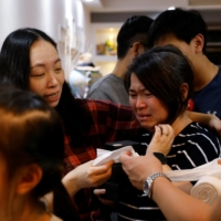 Asa Lai cries next to her friend during a farewell party for the Lai family before they emigrate to Scotland, at a friend's home in Hong Kong on Dec. 5. | REUTERS