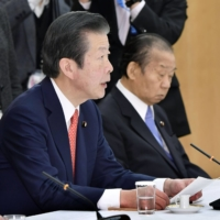Komeito Chief Representative Natsuo Yamaguchi (left) speaks next to LDP Secretary-General Toshihiro Nikai at a liaison meeting between the government and the ruling parties at the Prime Minister's Office on Dec. 7. | KYODO