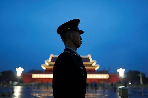 A paramilitary police officer stands guard during a flag-raising ceremony at Tiananmen Square on National Day, marking the 71st anniversary of the founding of People's Republic of China, in Beijing on Oct. 1. | REUTERS