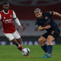 Manchester City's Sergio Aguero (right) shoots past Arsenal's Ainsley Maitland-Niles during their League Cup quarterfinal on Tuesday in London. | AFP-JIJI