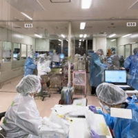 Medical staff take care of COVID-19 patients at a hospital in Tokyo. A survey showed that 15% of hospitals in Japan are seeing nurses quit because of a worsening working environment and discriminatory remarks made against them. | TOKYO MEDICAL AND DENTAL UNIVERSITY / VIA KYODO