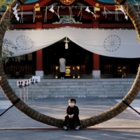 A boy sits on decorations for the New Year's holiday period at a Shinto shrine in Tokyo on Tuesday. Japan has one of the lowest rates of vaccine confidence in the world, according to a Lancet study, which found that fewer than 30% of people strongly agreed that vaccines were safe.  | REUTERS