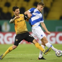 Dynamo's Philipp Hosiner (left) and Darmstadt's Lars Lukas Mai vie for the ball during their match in Dresden, Germany, on Tuesday. | AP