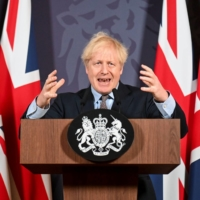 British Prime Minister Boris Johnson holds a news conference in London on Thursday.  | POOL / VIA REUTERS