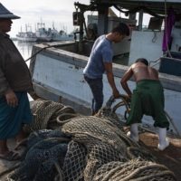 Migrant workers from Maynmar prepare a fishing boat in the Thai coastal province of Samut Sakhon in 2018. | AFP-JIJI