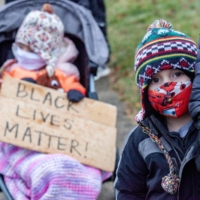 Black Lives Matter supporters and their children rally Thursday against the police killing of Andre Maurice Hill in the neighborhood where he was shot in Columbus, Ohio.  | AFP-JIJI