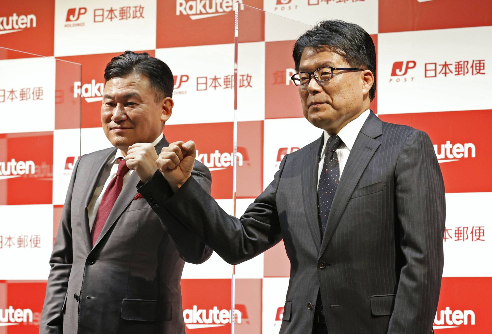 Rakuten Inc. Chairman and Chief Executive Officer Hiroshi Mikitani (left) and Japan Post Holdings Co. President Hiroya Masuda pose for a photo at a news conference in Tokyo on Thursday. | KYODO